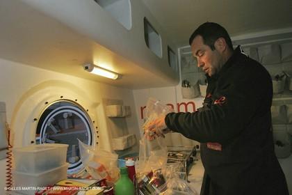 Orange II - Jules Verne Trophy 2004 - Jean-Baptiste Epron preparing food in the galley
