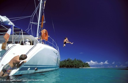 Boy jumping off the side of a catamaran into the sea